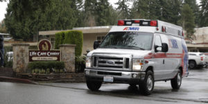 An ambulance leaves the Life Care Center in Kirkland, Wash., Friday, March 6, 2020. The facility is the epicenter of the outbreak of the the COVID-19 coronavirus in Washington state. (AP Photo/Ted S. Warren)