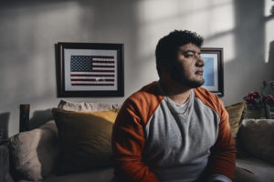 Man sitting in a darkened room, a small framed American flag on the wall behind